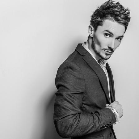 hombres maduros: Hombre apuesto joven elegante en traje gris. Blackwhite retrato de estudio de la moda.