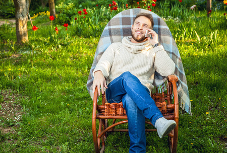 Handsome man relax in rocking-chair with plaid phone in a summer garden.