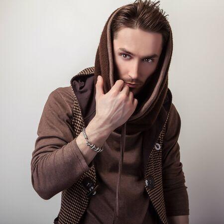 Attraktive junge Mann in einem braunen Pullover posieren im Studio. Standard-Bild