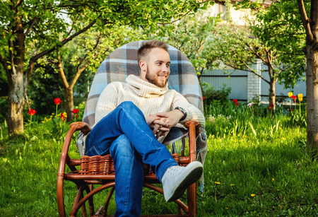 green man: Handsome man relax in rocking-chair with teapot  cup in summer garden.