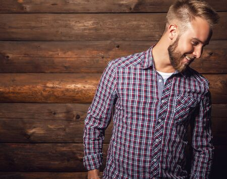 casual fashion: Portrait of young beautiful positive man against old wooden wall. Stock Photo