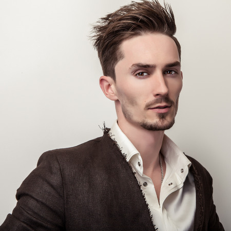 hombres guapos: Elegant young handsome man in long stylish coat. Studio fashion portrait.