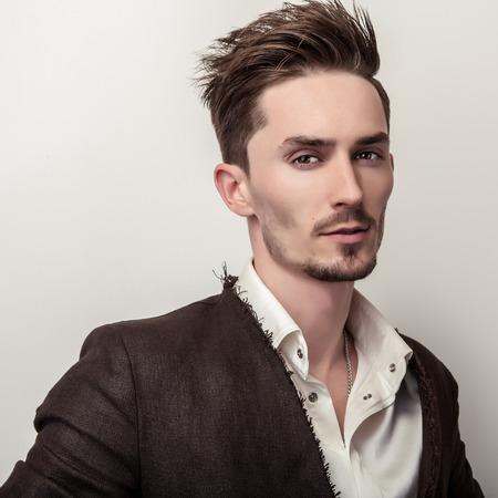 handsome men: Elegante giovane uomo bello in cappotto lungo elegante. Studio moda ritratto.