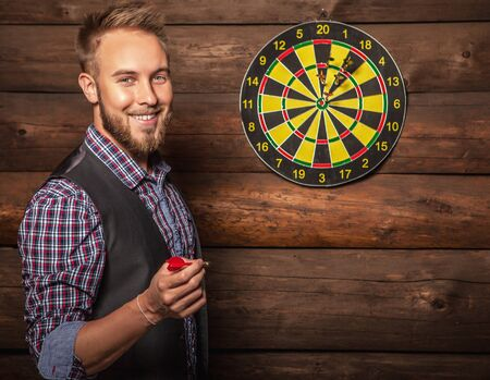 lucky man: Portrait of young friendly lucky man against old wooden wall with darts game. Concept: Hit in purpose. Photo.