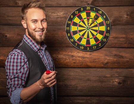 hombre con barba: Retrato de joven agradable hombre con suerte contra el antiguo muro de madera con juego de dardos. Concepto: Hit en el prop�sito. Foto.