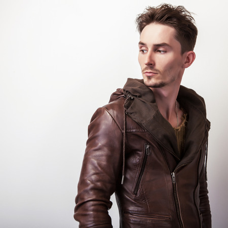Attractive young man in a brown leather jacket pose in studio.