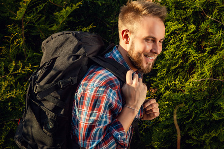marching: Young handsome man tourist traveler with a marching backpack poses against summer nature.