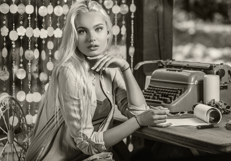 entries: Beautiful young blonde sits in arbor at oak table near vintage typewriter  makes entries in sheets of paper. Sepia photo.