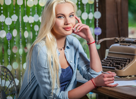 entries: Beautiful young blonde sits in arbor at oak table near vintage typewriter  makes entries in sheets of paper. Stock Photo