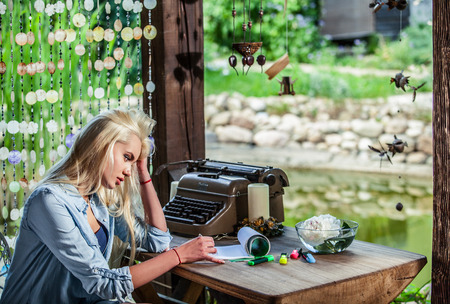 maquina de escribir: Joven rubia hermosa se sienta en el cenador en la mesa de roble cerca de la máquina de escribir del vintage hace entradas en hojas de papel. Foto de archivo