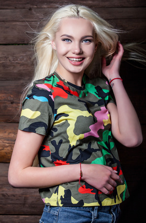 clothing model: Beautiful young blonde in bright color camouflage undershirt poses on wooden background.