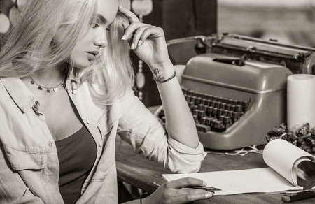 vintage portrait: Beautiful young blonde sits in arbor at oak table near vintage typewriter  makes entries in sheets of paper. Sepia photo.