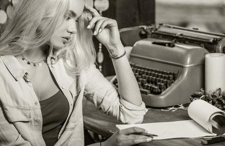maquina de escribir: Joven rubia hermosa se sienta en la glorieta en la mesa de roble cerca de la máquina de escribir del vintage hace entradas en hojas de papel. Foto de la sepia. Foto de archivo