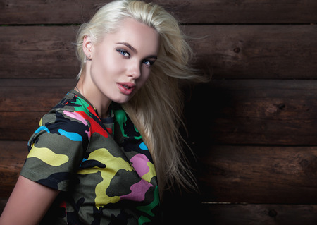 undershirt: Beautiful young blonde in bright color camouflage undershirt poses on wooden background.