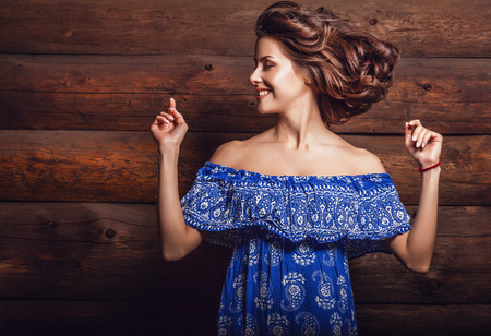 color hair: Attractive young brunette beauty woman in blue casual dress pose against wooden background.