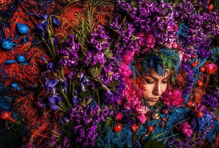 Fairy tale girl portrait surrounded with natural plants and flowers. Art image in bright fantasy stylization. photo
