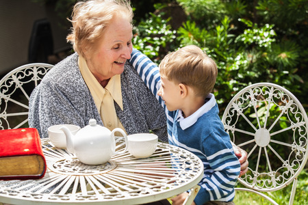 grandmother and children: Positive grandmother and grandson spent time together in summer solar garden.