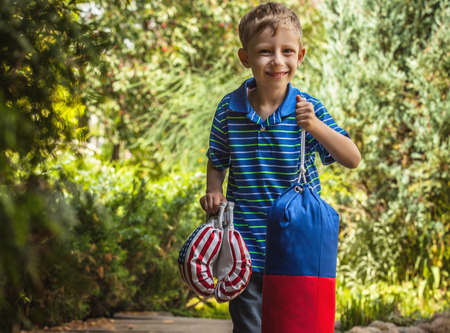 punching bag: Outdoor portrait of positive little boy in sunny summer garden with childrens punching bag and gloves. Stock Photo
