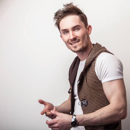 Studio portrait of young handsome man in design brown vest.