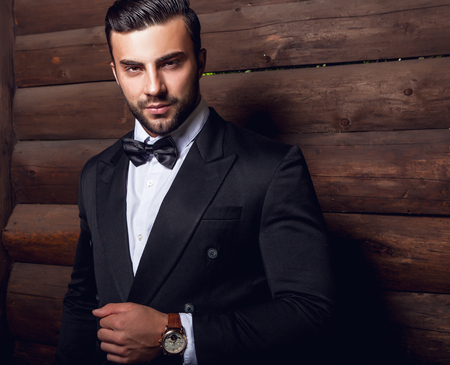 moda: Retrato do homem elegante bonita de encontro à parede de madeira Em terno laço preto.