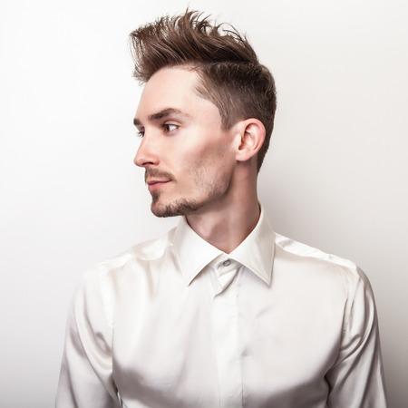 hombres negros: Hombre apuesto joven elegante en camisa de seda blanca. Retrato de moda Studio.