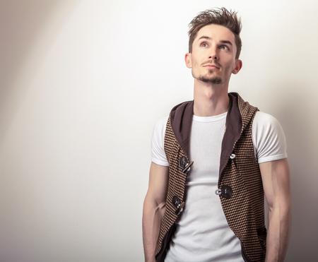 musculine: Studio portrait of young handsome man in design brown vest.