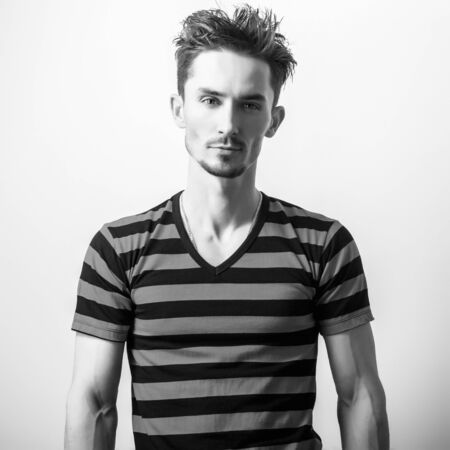 male beauty: Black-white studio portrait of young handsome man.