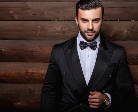 hairstyles: Portrait of young beautiful fashionable man against wooden wall In black suit  bow tie. Stock Photo