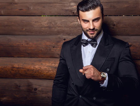 relaxed man: Portrait of young beautiful fashionable man against wooden wall In black suit  bow tie. Stock Photo