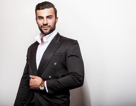 hombres jovenes: Hombre apuesto joven elegante en el cl�sico traje negro. Retrato de moda Studio.