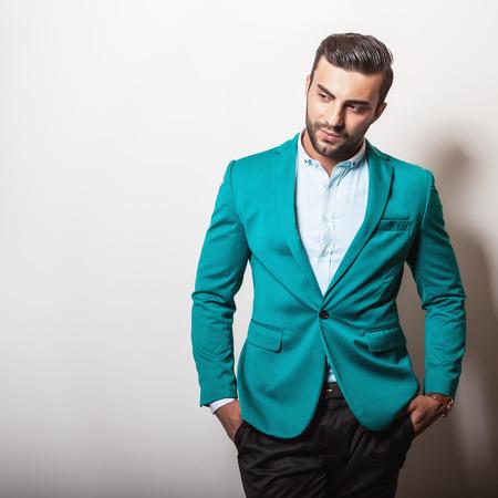 azul turqueza: Hombre apuesto joven elegante en la chaqueta de color turquesa con estilo. Retrato de moda Studio.