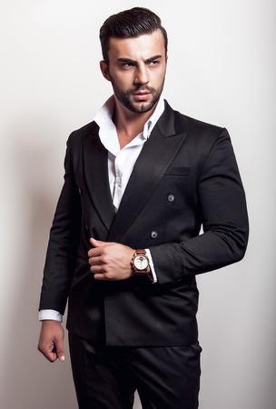 beau mec: Elégante jeune bel homme dans le classique costume noir. Studio de portrait de la mode.