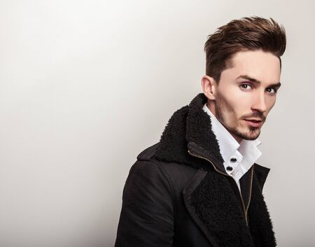 young style: Elegant young handsome man in long stylish black coat. Studio fashion portrait. Stock Photo