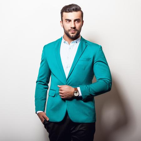 stylish men: Elegant young handsome man in stylish turquoise jacket. Studio fashion portrait. Stock Photo