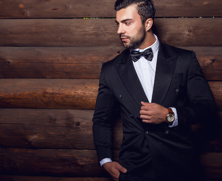 alone in the dark: Portrait of young beautiful fashionable man against wooden wall In black suit  bow tie. Stock Photo