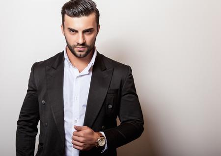Elegant young handsome man in classic black costume. Studio fashion portrait.