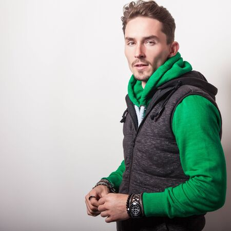 hooded vest: Emotional portrait of attractive young man in a grey vest  green sweater with a hood. Studio photo.
