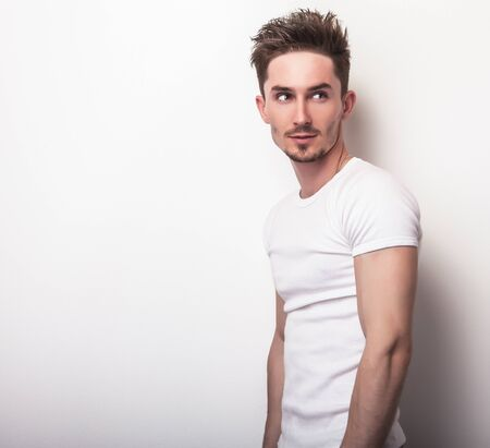 Studio portrait of young handsome man in casual white t-shirt.