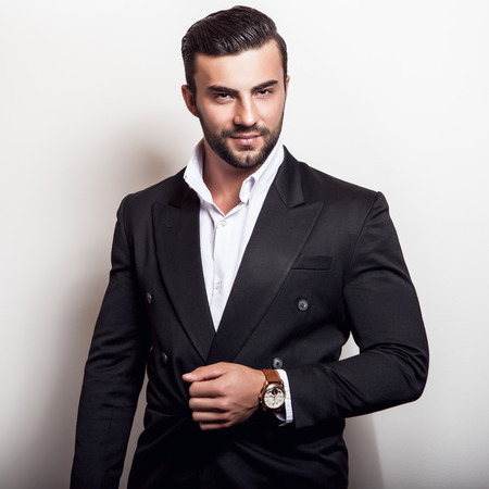 bel homme: El�gante jeune bel homme dans le classique costume noir. Studio de portrait de la mode.