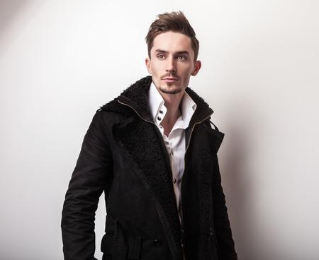 hombres negros: Elegant young handsome man in long stylish black coat. Studio fashion portrait. Foto de archivo