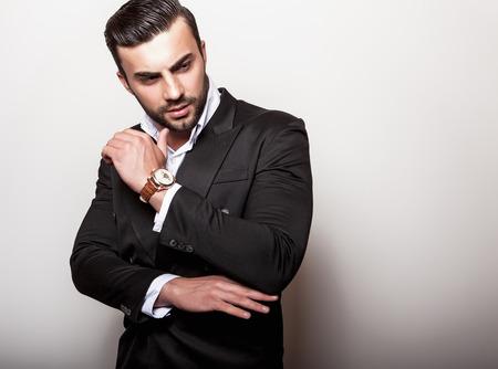 male costume: Elegant young handsome man in classic black costume. Studio fashion portrait.