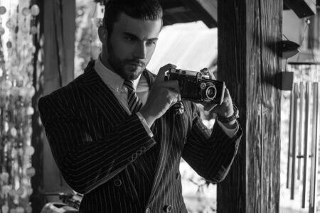 staring at the camera man: Young fashionable man with retro camera.
