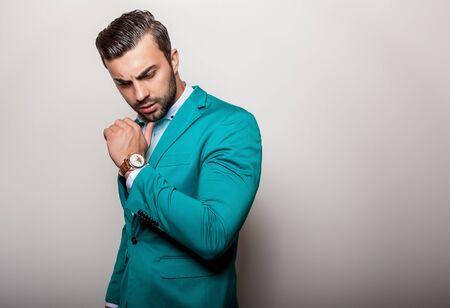 color: Elegant young handsome man in stylish turquoise jacket. Studio fashion portrait. Stock Photo