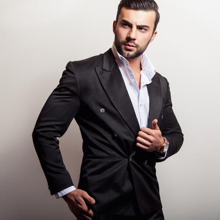 cool guy: Elegant young handsome man in classic black costume. Studio fashion portrait.