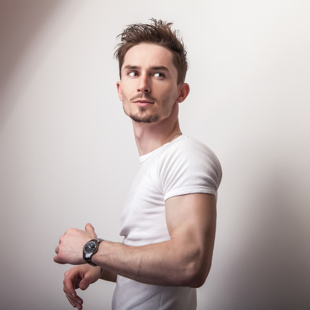 musculine: Studio portrait of young handsome man in casual white t-shirt.