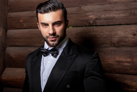 young male: Portrait of young beautiful fashionable man against wooden wall In black suit  bow tie. Stock Photo