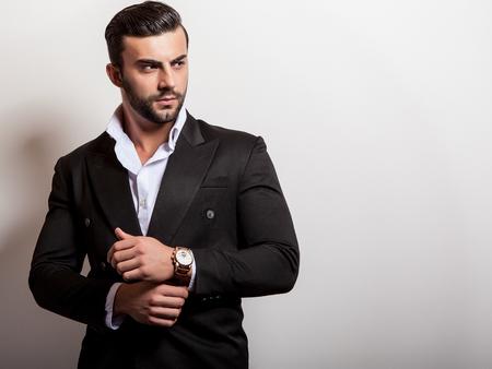 古典的な黒ずくめのエレガントな若いハンサムな男。ファッションのスタジオ ポートレート。
