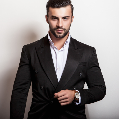 modelos masculinos: Hombre apuesto joven elegante en el clásico traje negro. Retrato de moda Studio.