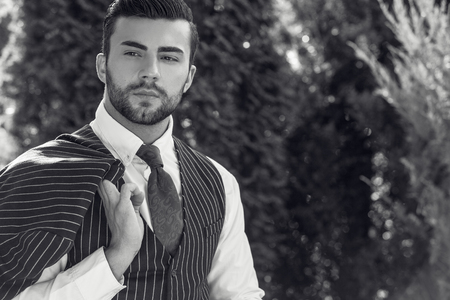 black shadow: Black-white portrait of young beautiful fashionable man in classic vest in summer lodge. Stock Photo
