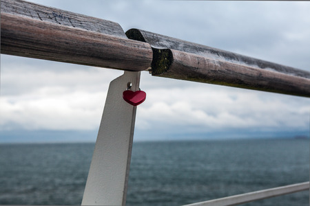 tools construction: Old handrail against north sea with lock in form of heart.